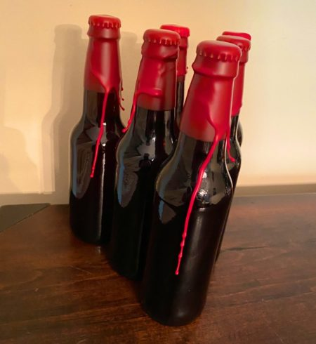Bottles of home brew with waxed caps